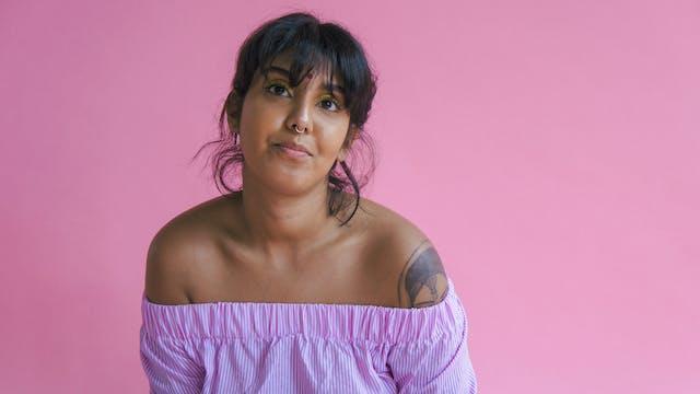 Portrait of Demi Nandhra on a pink background.