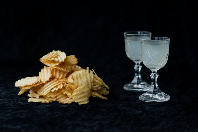 Photograph of a pile of crisps on the left and two crystal cut glasses containing lemonade on the right. The background is a black velvet material.