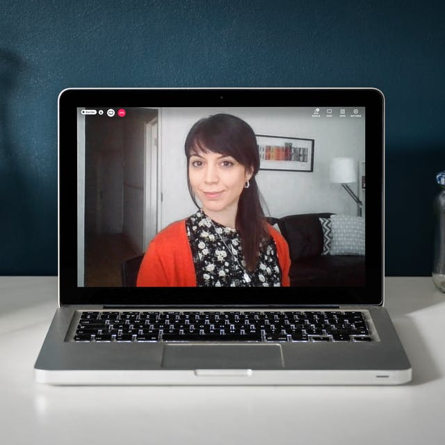 Photograph of a laptop on a desk. On the laptop screen is a live event showing the speaker, Sara Masinelli with a red telephone icon in the top left-hand corner of the screen. She has dark brown hair with a fringe and her hair is tied up. She is wearing a bright red cardigan with a floral top. She is sitting in a living room with a dark sofa behind her. Around the laptop there is a teapot, jam jars, and an empty glass vase with some green leaves from a houseplant coming into view at the left-hand edge of the desk.