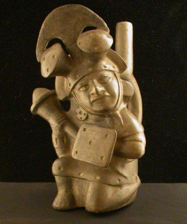 Photograph of a ceramic sculpture of a warrior, kneeling on left knee, bearing square shield on left arm and massive club in right hand. Wears elaborate helmet with crosswise crest, crescentic blade and two mushroom knobs.