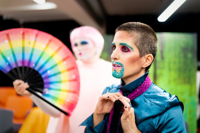 Photograph showing a performer backstage. The performer is dressed in a shiny blue shirt. They are in the process of tying their purple tie. Their mouth and eye brows are covered in blue glitter make-up. In the background is another performer holding a large rainbow coloured hand fan.