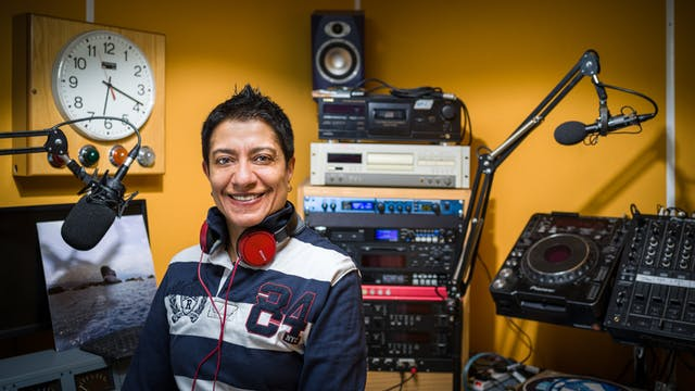 Photographic Portrait of a female DJ in a small Dj booth at a radio station. Behind the woman is radio equipment and a clock on the yellow sound absorbing wall.