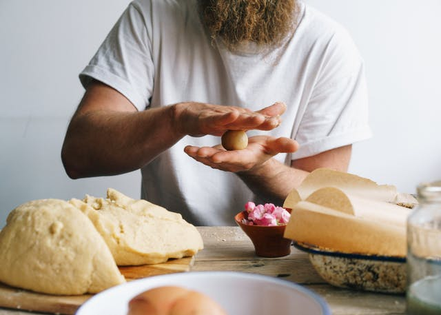 Photograph of a man sat at a wooden kitchen table. Only his torso can be seen along with part of his long beard. He is wearing a white t-shirt. On the tabletop is a dough mixture, a small bowl of flower heads and baking trays lined with greaseproof paper. The man is in the process of rolling the dough into small ball shapes with his hands.