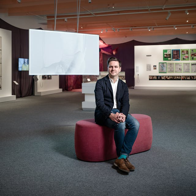 Photograph of Misbehaving Bodies curator George Vasey sitting in the exhibition space.  Behind him are the works of Jo Spence; in the form of photographs and tear sheets hung on white panels, and Oreet Ashery; in the form of a projection of a white figure moving against a white screen.