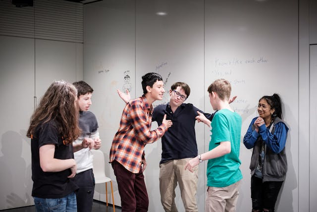 Photograph of a group of young people taking part in an improv comedy workshop as part of the Wellcome Collection Raw Minds programme.