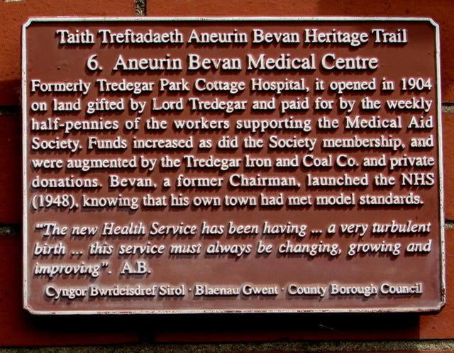 """Photograph of the commemorative plaque that forms part of the Taith Treftadaeth Aneurin Bevan Heritage Trail. Plaque reads: """"Aneurin Bevan Medical Centre. Formerly Tredegar Park Cottage Hospital, it opened in 1904 on land gifted by Lord Tredegar and paid for by the weekly half-pennies of the workers supporting the Medical Aid Society. Funds increased as did the Society membership, and were augmented by the Tredegar Iron and Coal Co. and private donations. Bevan, a former Chairman, launched the NHS (1948), knowing that his own town had met model standards."""
