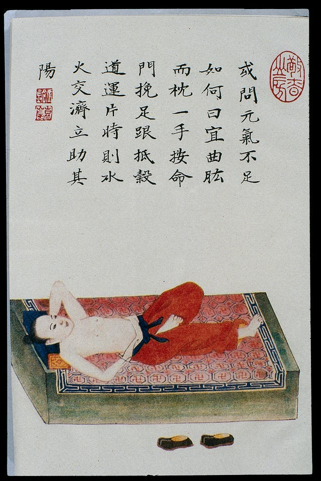 Painting showing a person wearing red trousers reclining on a bed. They are barefoot and shirtless and have one arm behind their head and one leg curled up towards their body, and their shoes are in front of the bed.