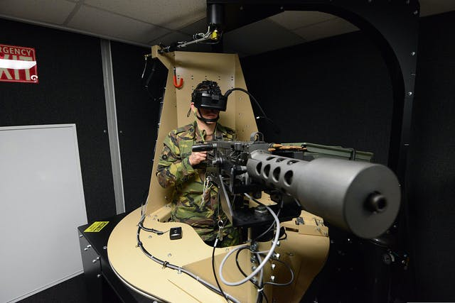 Colour photograph of a man wearing green camouflage clothing with a headset over his eyes and holding a device shaped like a large machine gun and covered in wires.