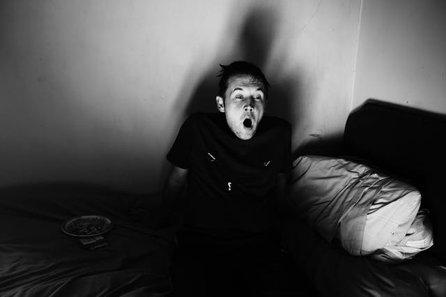 Black and white photograph showing a man sitting sideways on a bed, yawning. The lighting in the room is from a low angle casting his shadow on the wall. Beside him on the bed is a plate of food.