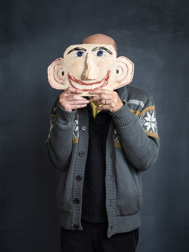 Photograph of stroke survivor and artist Chris Miller in an artist studio. A grey textured background frames the artist as he holds a ceramic of a head, which acts as a cartoon likeness of his own face and which obscures his own face.
