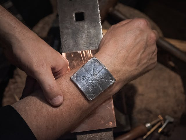 Photograph of the lead healing plate placed on the wrist of a man.  The wrist is resting on an anvil. Inscribed on the lead plate are five crosses, representing the five wounds of Christ.