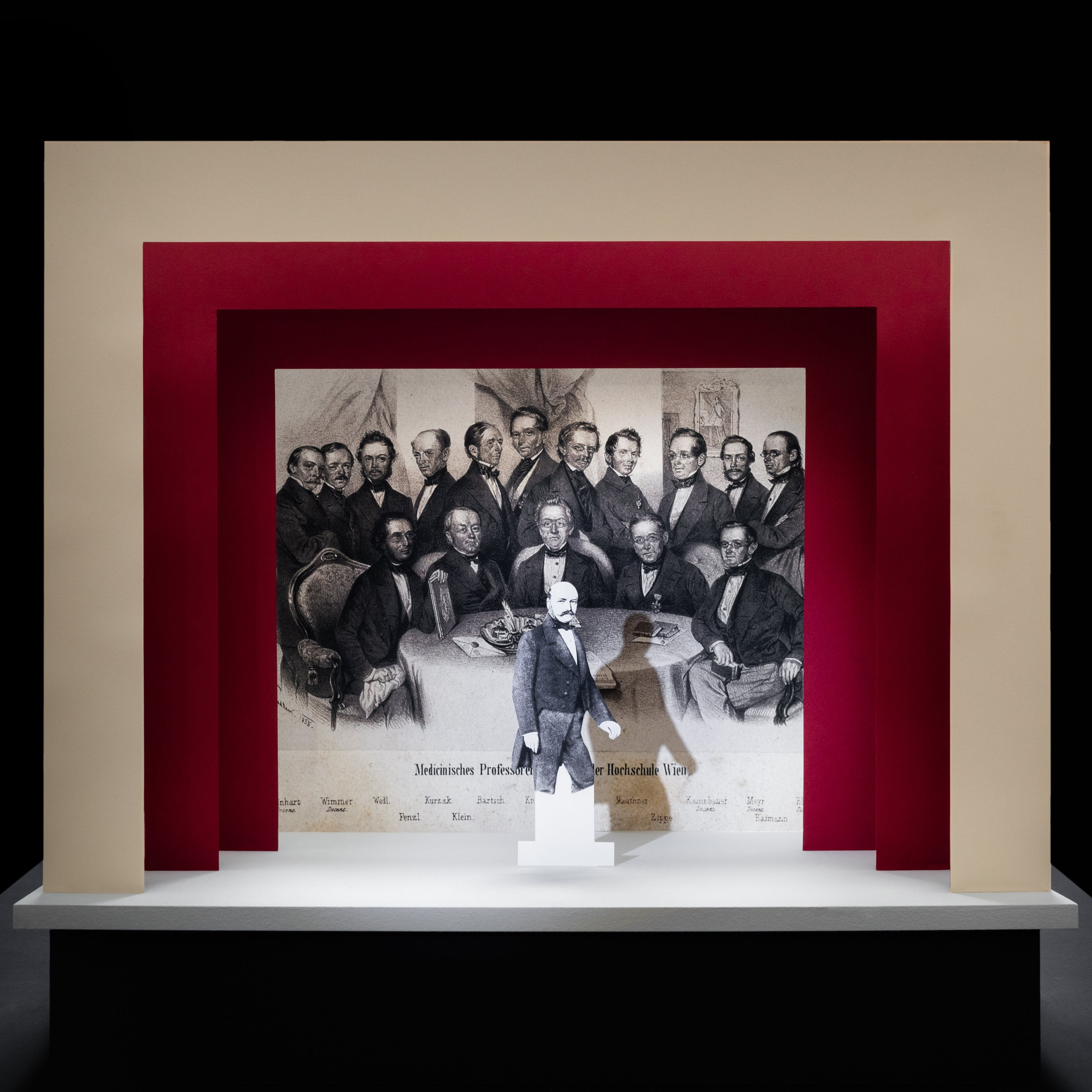 Photograph of a simple theatre stage set, made out of card. The background surrounding the stage is black. The stage floor is white and the framing of the stage is made out of 3 square edged arches, each one smaller than the other, receding backwards. The first arch is cream coloured and the other two are a red. On the stage is a small cut out illustration of a man with a moustache from the early 20th century. Behind him forming the backdrop is a black and white drawing of a group of suited men gathered around a table looking towards the viewer. Under these men are a list of their names.