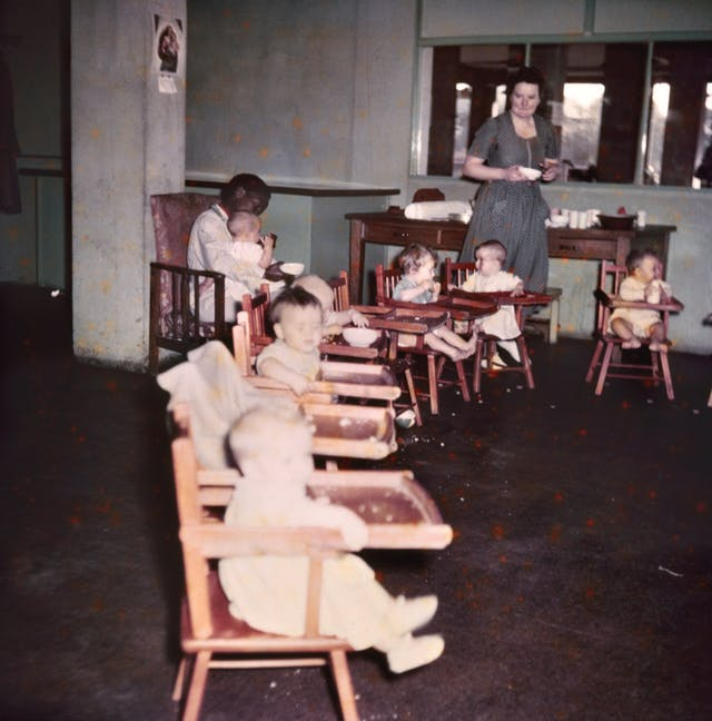 Photograph from the mid-20th Century Peckham Pioneer Centre, showing a long row of eight high-chairs, six of which are occupied by infants who are eating or drinking. Behind them, a woman sits in a chair with a child on her lap and a bowl in her hand, and another woman approaches from behind holding another bowl.