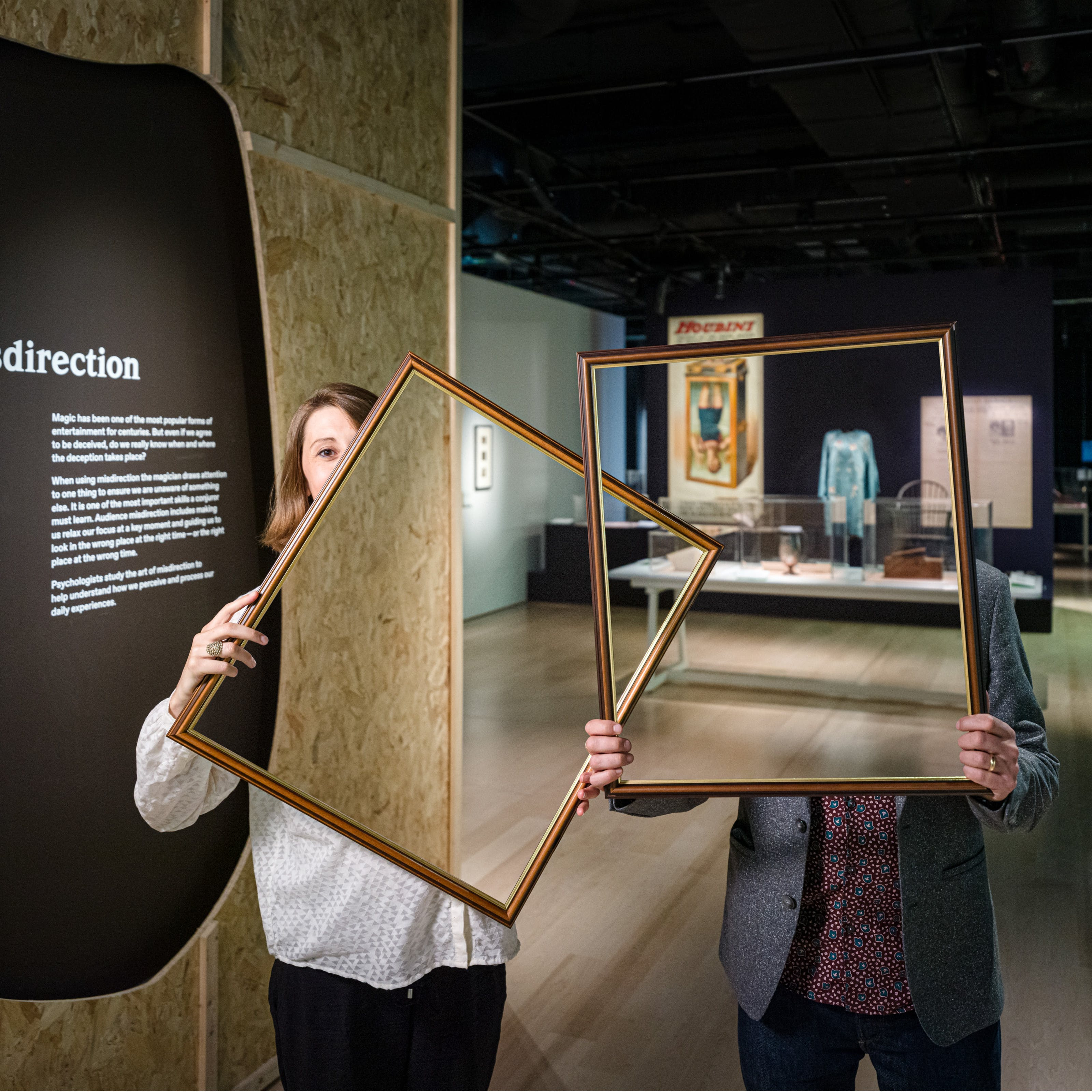 """Photograph of a woman and a man in a dark gallery space holding up picture frames in front of their bodies and parts of their faces. Within the picture frame you can see straight through them, as if their bodies and faces have disappeared. In the background you can see a large historical poster and exhibitor display cases. On the left is a text panel titled, """"Misdirection""""."""