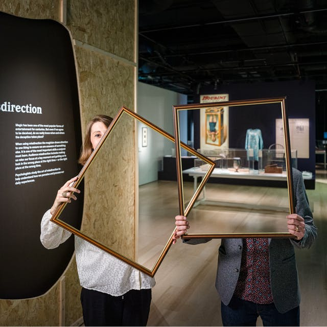 "Photograph of a woman and a man in a dark gallery space holding up picture frames in front of their bodies and parts of their faces. Within the picture frame you can see straight through them, as if their bodies and faces have disappeared. In the background you can see a large historical poster and exhibitor display cases. On the left is a text panel titled, ""Misdirection""."
