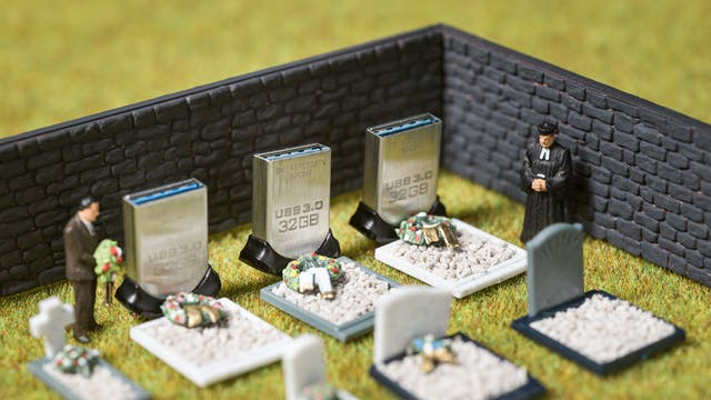 Photograph of model railway scenery depicting a walled cemetery containing seven graves. Models of a man holding flowers and a clergyman strand over the graves. Three of the headstones are made of actual size USB memory sticks standing on their ends. On the sticks is the text, USB 3.0, 32GB.
