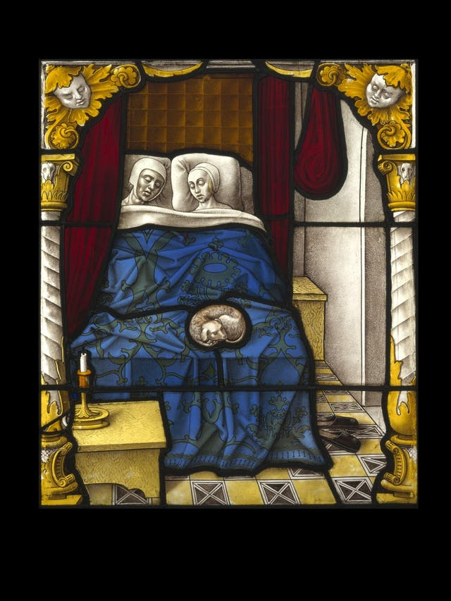 Image of a stained glass panel depicting a man and a woman in bed. They lie sleeping, with night caps on, in their bed which is covered with a deep blue brocaded bed spread. Behind them is a red curtain. On their bed is a small dog asleep. A table with a candlestick and candle is in the front left of the panel and a single pair of heeless shoes lie on the floor to the right.