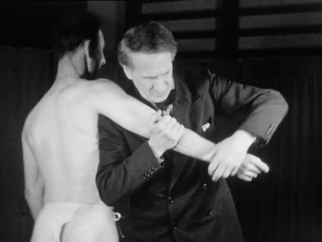 Black and white still from a film showing a man in a suit manipulating the right arm of an almost naked man.
