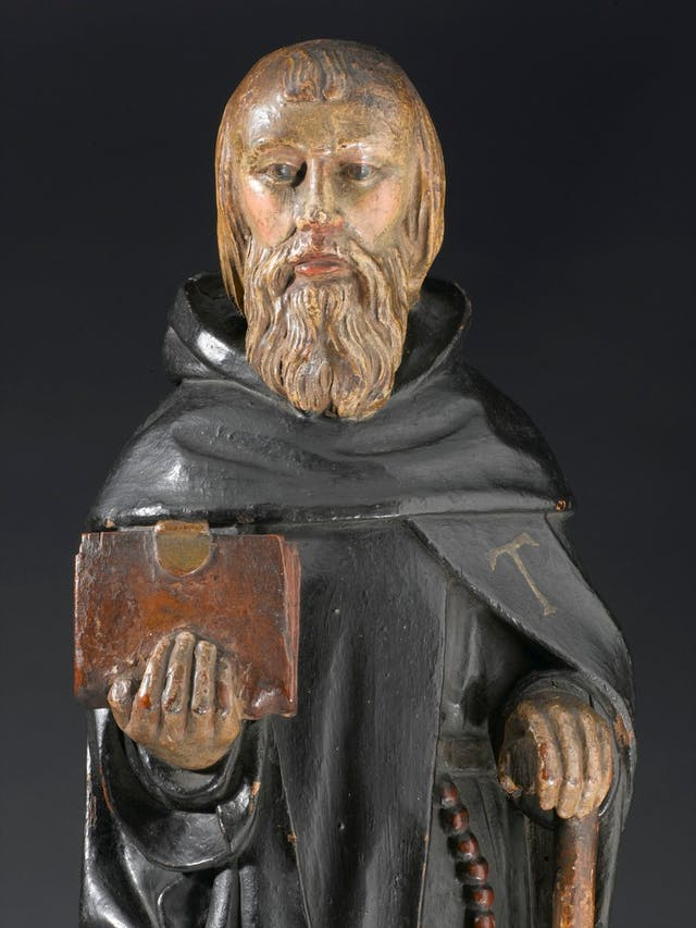 Photo of statue of bearded man holding a book