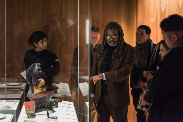 Photograph of a man in a dark gallery space in front of a display case, pointing towards an object inside. He is surrounded by a small group of people who are listening to what he has to say.