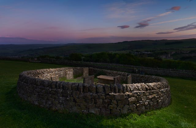 Photograph of rural landscape at dusk, with a circular dry stone walled enclosure, housing several grave stones.