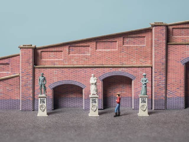 Photograph of model railway scenery depicting a tapered brick wall in front of which are three statues on plinths. Under each statue is a carved wreath with their name in the middle and a printed QR code. A model figure stands looking at the statue in the middle.