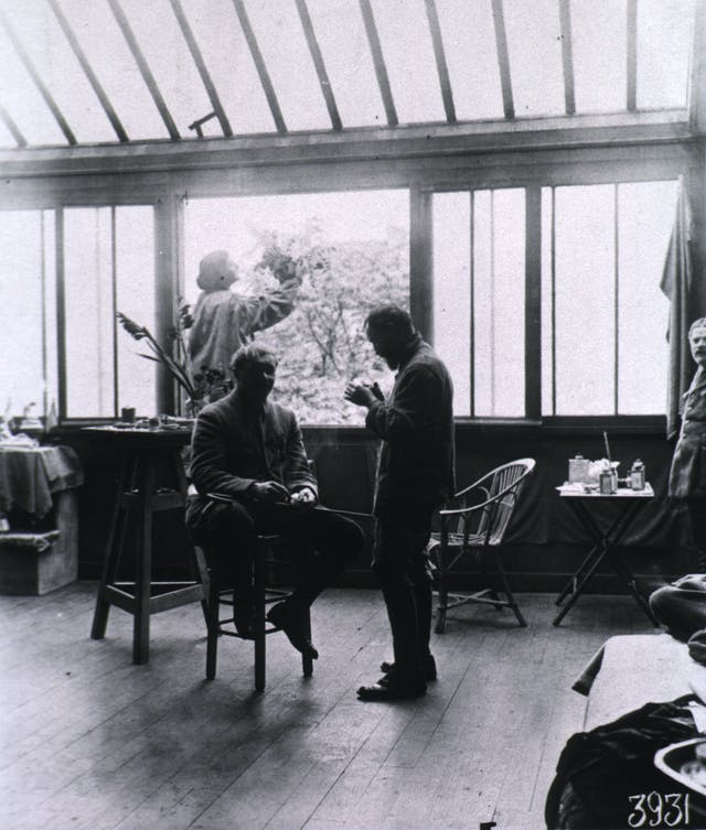 Black and white photograoh of a sunlit stiudio with two standing figures and one seated figure.