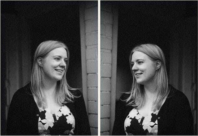 Photographic black and white diptych. The images both show the same young woman with blond hair, wearing a floral dress and black cardigan, standing outside a front door and white brickwork. In each image she is pictured in profile, looking towards herself in the other image, as if in a mirror. In both images the woman is smiling.