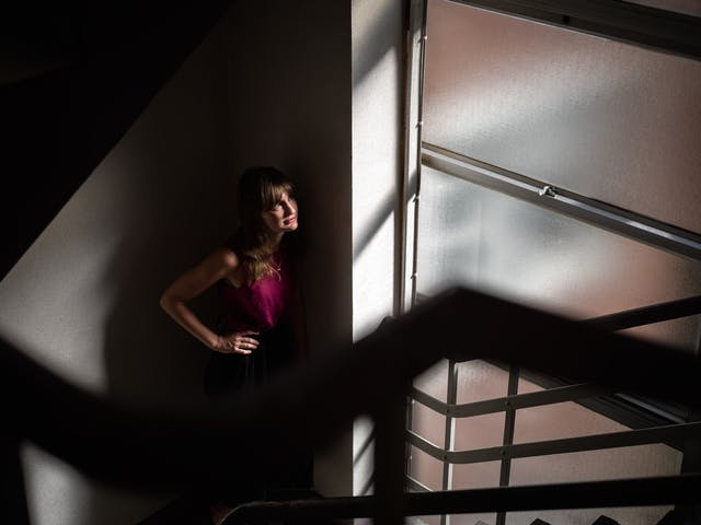 Photograph of a woman in a red blouse in a stairwell, looking out of a large full sized window.  The sunlight is casting a hard shadow largely covering her entire body, with only a sliver of her face, torso and arm being lit.  The hard, dark shadows give a sense of apprehension and eeriness.