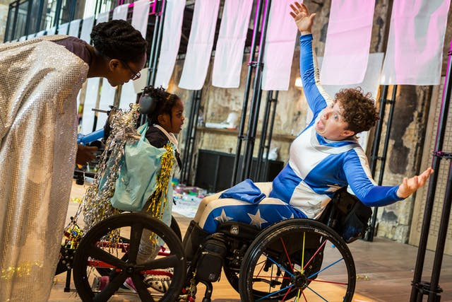 Photograph at an event showing a woman in a wheelchair wearing a blue and white superhero style outfit, with her arms outstretched and her mouth wide open. A mother and daughter are stood in front of her, watching.