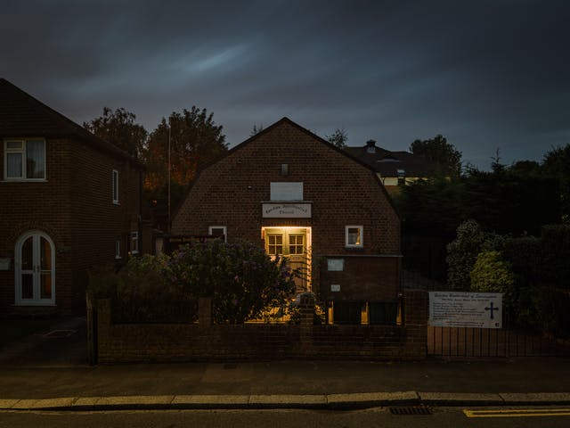 Photograph of Garston Spiritualist Church, Watford, at night.  Set in a residential setting the double doors of the church are lit by a porch light, which is also spilling into the small yard.  The church is partially hidden by a brick wall come gate, and two bushes.