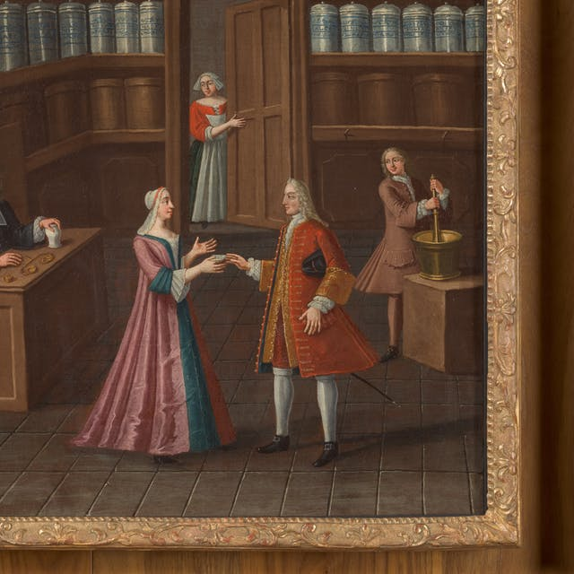 Photograph of a section of an oil painting in a gilded ornate frame, against a wood panelled wall.  The painting depicts a pharmacy circa 1700.  The walls of the shop are lined with blue and brown vases.  There are five figures in the painting in period clothing. A gentleman in a top hat is sat at a desk with a hand on a small vase. A maid is half showing, peering through a door.  Another gentleman is stirring a golden pot with a large ladle.  The final two figures of a lady and an officer are interacting in the centre of the painting.