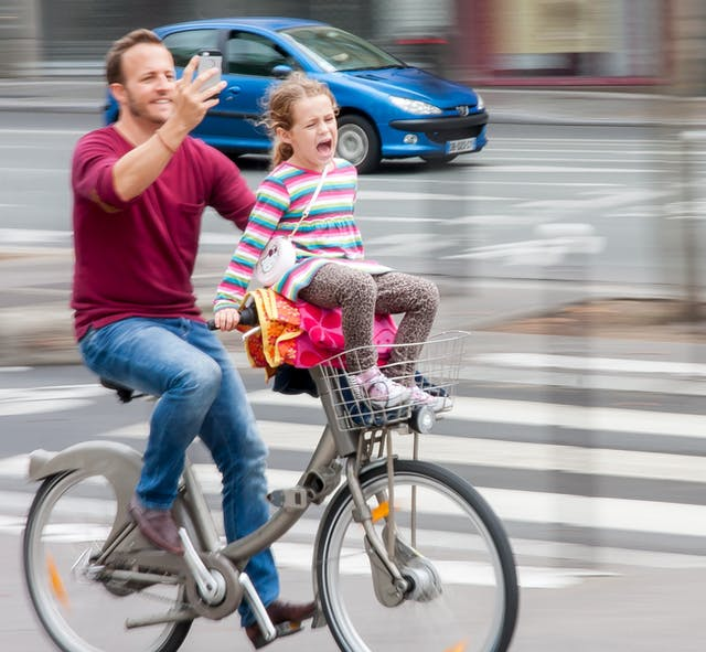 Photograph of a man riding a bicycle taking a selfie whilst the girl sitting on his handlebars appears to be crying or screaming. Blurred background and car behind indicate movement.