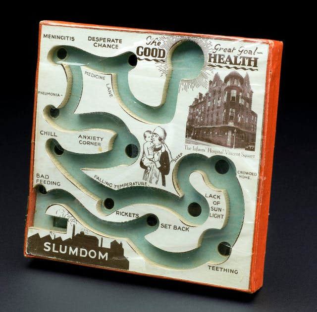 """Board with a track in it and various holes for a small ball to fall into. The track begins at Slumdon and ends and """"The Great Goal - Good Health""""."""