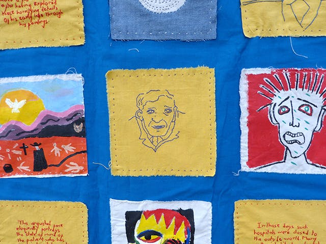 An embroidered face and painted squares of calico from a wall hanging by Beth Hopkins, inspired by the Adamson Collection at Wellcome.