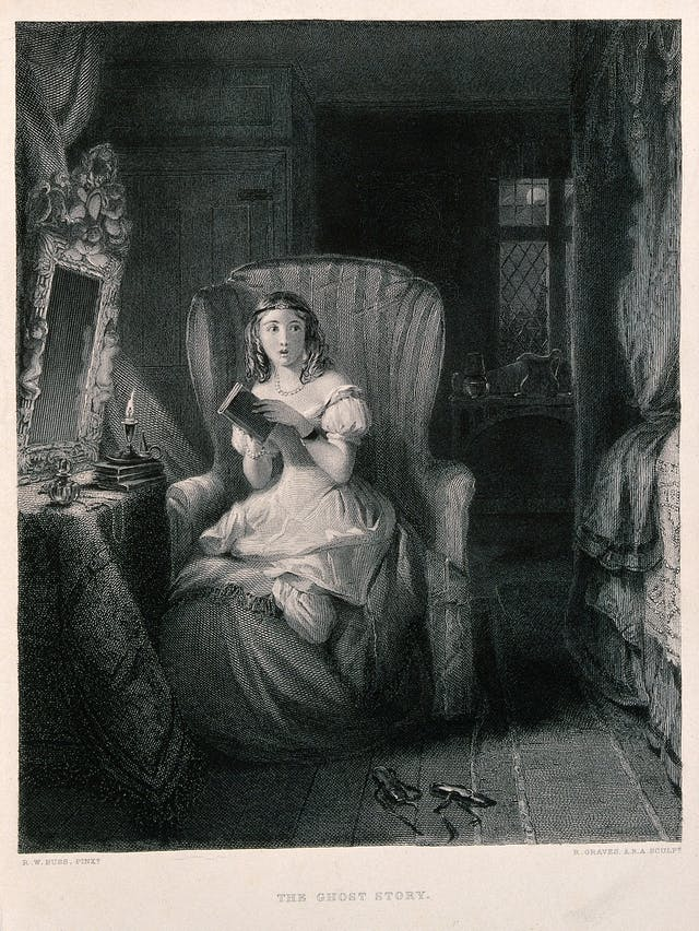 A young woman is sitting in a chair reading a story which has made her nervous