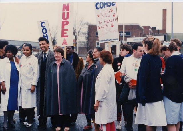 Colour photograph of people gathered at a strike. Many wear nurses