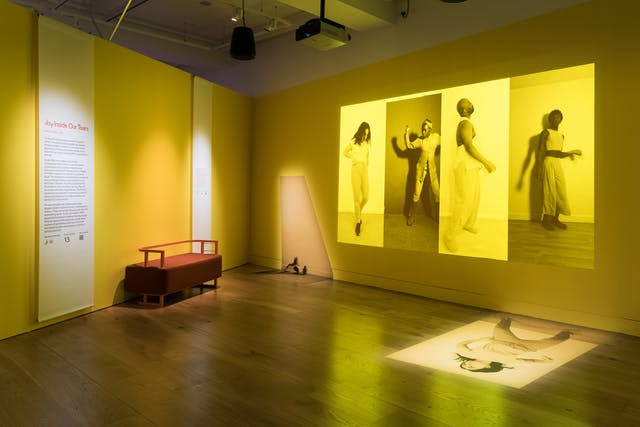 Photograph of an exhibition gallery space showing two walls meeting at right angles and a wooden floor. One the left hand wall is an information panel and bench seat. On the right hand wall is a projection of four large vertical photographs placed side to side, each monotone, but with a bright yellow tone overlaid. Each image shows an individual in a performative pose. The overall tones of the projection and the gallery walls are yellows.