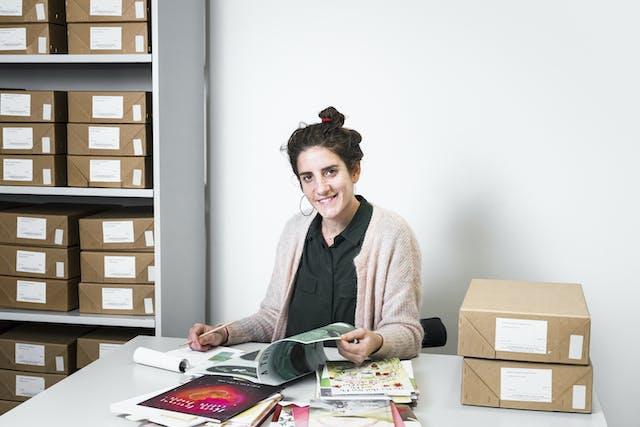 西格丽德·弗托曼博士坐在威康图书馆的档案箱和从档案收集的文件和出版物的选择