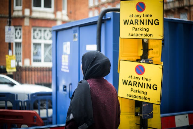 """Photograph of a woman wearing a black head scarf facing away from the camera towards a street scene containing a blue building site storage container and two large yellow signs which say, """"(no stopping symbol) at any time WARNING Parking suspension""""."""