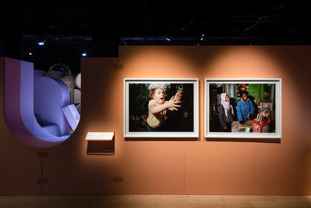 Photograph of an orange coloured exhibition wall showing 2 framed photographs. The photograph on the left shows a young girl reaching out to catch a frog. The photograph on the right shows two young people dressed in winter clothes sawing a section of wood.