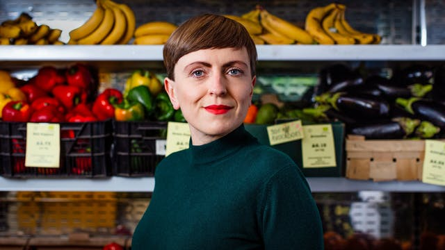 Photographic portrait of Elsa Richardson in front of a display of fruit and vegetables in a whole food shop.