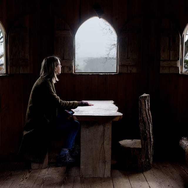 Photograph of a young woman sitting at a wooden table in a hermitage. On the other side the table is an empty chair carved from a tree trunk. behind her are three small arched windows which show the trees and mist outside.