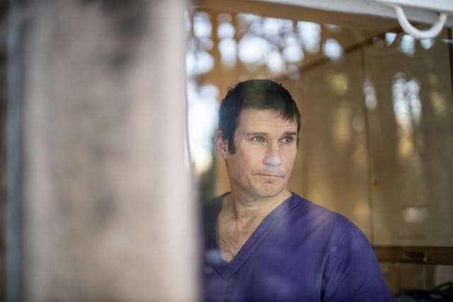 Photograph of a man from the chest up wearing blue medical scrubs. The photograph has been taken through a glass window and the man is gazing out of the window off to camera right, lips pursed.  Reflected in the window can be seen the out of focus blur of trees and sky. To the right is the also out of focus stone edge of the building.