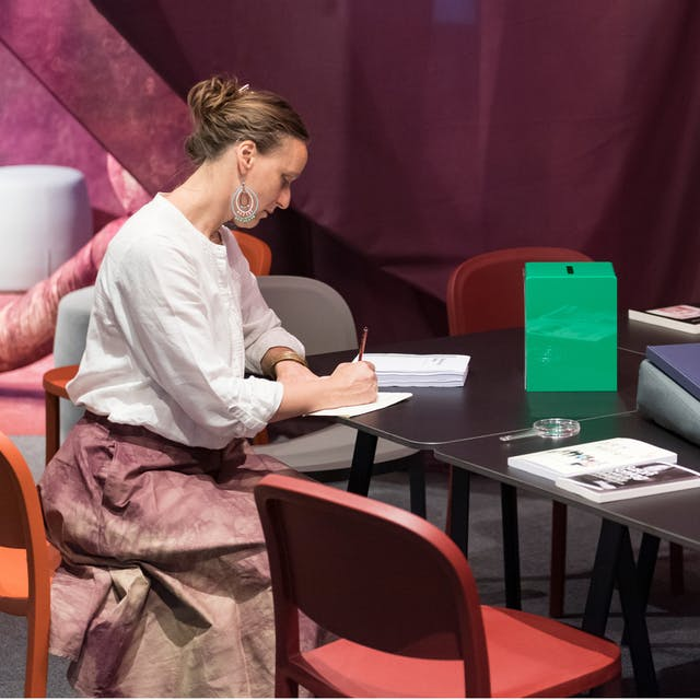 Photograph of a person sitting at a table within the Misbehaving Bodies exhibition at Wellcome Collection. They are holding a pencil and writing on a piece of paper. There are several books scattered around the table.
