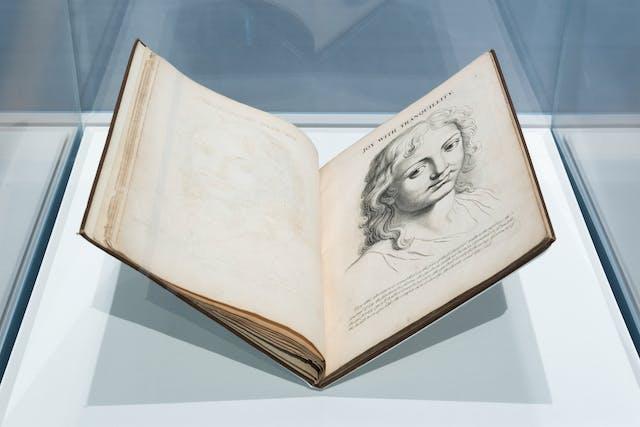 照片的一个展览玻璃展示柜显示一个打开的旧,早期印刷的书,在一个书摇篮。张开的两页展页上有一个人物的肖像雕刻