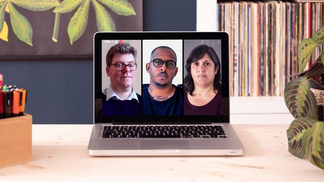 """Photograph of a laptop on a wooden desk with a pot of pens and a houseplant. The laptop screen is displaying portraits of two men and a woman. There are video call icons """"People"""" and """"Chat"""" at the top of the screen and a red telephone icon."""