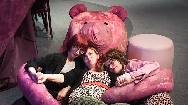 The artist Amanda Millis holding hands with two people on the floor lying down in the arms of a giant purple teddy bear in Wellcome Collection