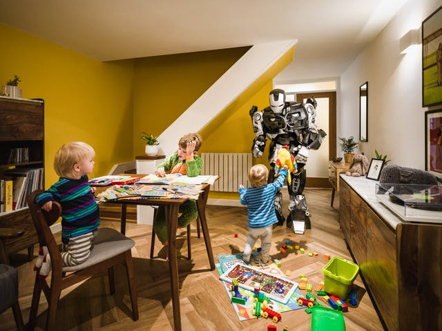 Photograph of a living room with two small toddlers and an older boy playing with puzzles, bricks and colouring books. In the background is a large robot bending down to receive a soft toy that now of the toddlers is handing it.