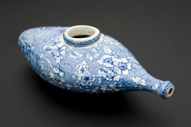 Colour photograph of an infant feeding bottle from the 19th century, which is a rounded ceramic shape with blue and white flowers painted on and a large hole at the top and a smaller one at the side for the infant to suckle.
